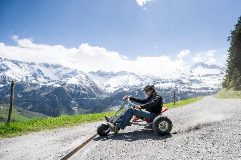Üsé Meyer fährt auf einem Mountain-Cart in Elm den Berg hinab. im Hintergrund die Tschingelhörner mit dem Martinsloch, die zur Tektonikarena Sardona gehören..Foto: Samuel Trümpy.