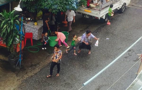 Wasserspaß in den Straßen: jeder Fußgänger bekommt eine Ladung Wasser ab.