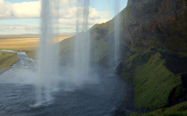 Auf einem felsigen Pfad kannst du den Wasserfall Seljalandfoss auch von hinten ansehen.